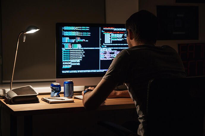 Back view of modern programmer sitting and writing code in dark room